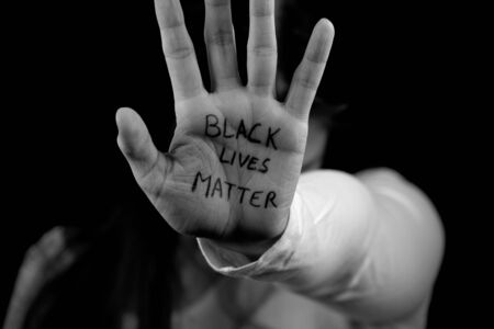 Black and white picture of Caucasian girl extending hand with Black Lives Matter written on it Banque d'images
