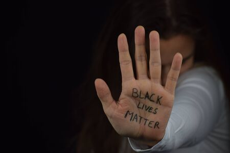 White female showing palm with BLM slogan to protest against racism