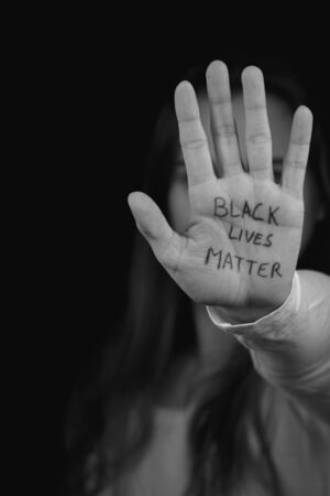 Black and white portrait of a white woman with Black Lives Matter written on her palm