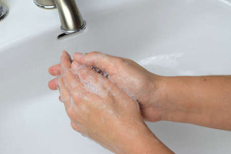 Female washing hands in white tap. Wash your hands often to kill virus and germs