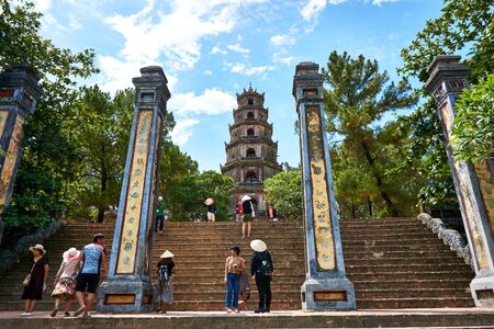 HUE, VIETNAM - JUNE 20, 2019 - People visit he Thien Mu Pagoda in the former Vietnamese capital of Hue on the Perfume River.