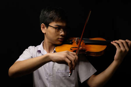 Young Asian man playing violin on dark background