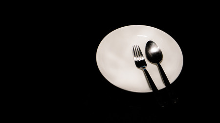 fork and spoon on plate at black table Stock Photo