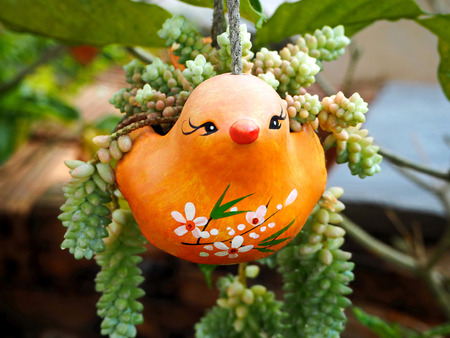 Orange Ceramic Bird Hanging Planter in the Garden