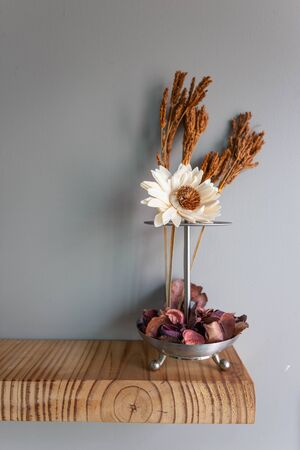Home interior decor in grey walls and wood table : stainless vase with dry flowers, Living room decoration. Rustic still life.
