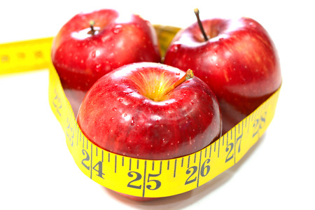 Healthy diet with apples and measuring tape. They are the healthiest food with high in dietary fiber, antioxidants and vitamins. They are recommended by doctors for a healthy diet.