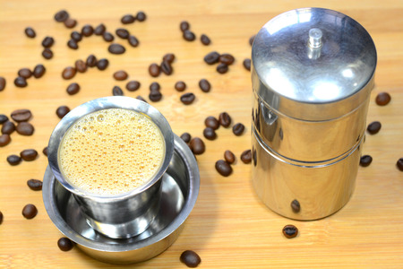 Madras filter coffee with coffee beans and coffee filter. Madras filter coffee is famous filter coffee in India.