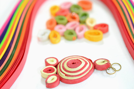 Quilling paper and craft activities. Closeup of ear ring made of quilling paper. Stock Photo