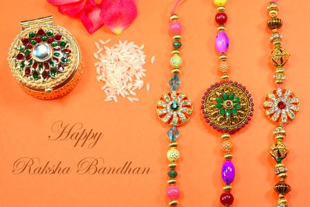 Celebrating Indian hindu festival Raksha Bandhan. Colorful Rakhi with flowers and rice on a orange background.