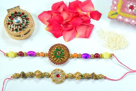 Celebrating Indian hindu festival Raksha Bandhan. Colorful Rakhi with flowers and rice on a white background.