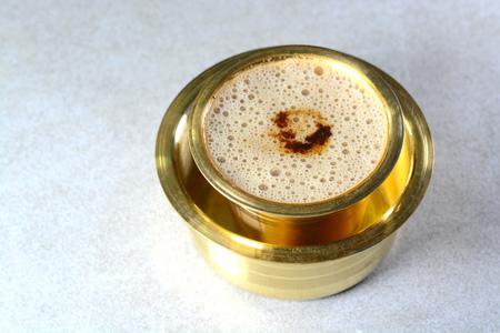 Indiase filterkoffie geserveerd in koperen kop en schotel Stockfoto