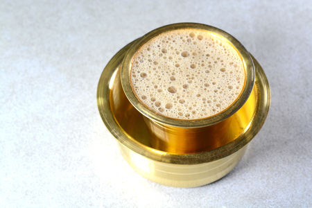 Indian Filter Coffee served in brass cup and saucer