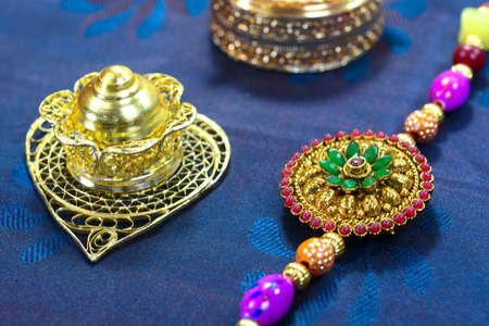Celebrating Indian festival Raksha Bandhan. Colorful rakhi with stones on silk background