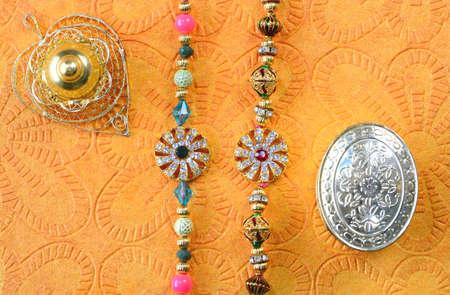 Celebrating Indian festival Raksha Bandhan. Colorful rakhi with stones on yellow background Stock fotó