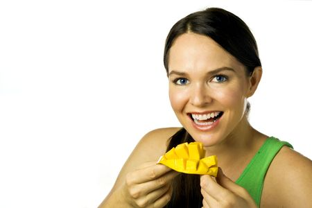 mango isolated: Young beautiful and happy woman eating a mango isolated over white