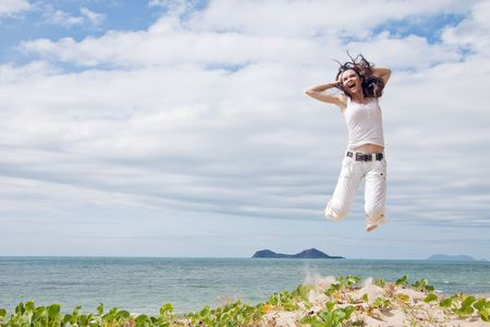 A beautiful girl jumping and laughing on a sunny tropical beach