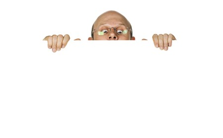 Funny portrait of curious man looking over white wall or sign. Isolated over white.