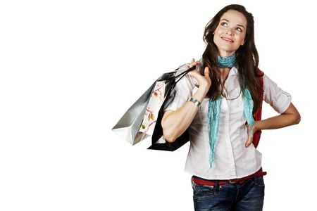 A beautiful portrait of a young attractive woman holding shopping bags and looking contemplative. Isolated over white. Stock Photo - 7221345