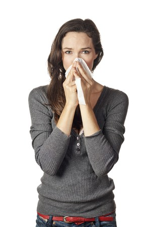A woman with a cold or allergy wiping or blowing her nose. Stock Photo