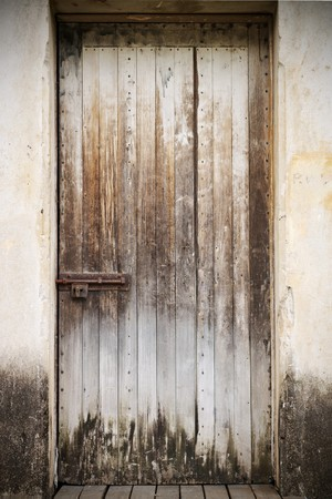 An old closed rustic wooden front door with a rusty lock photo