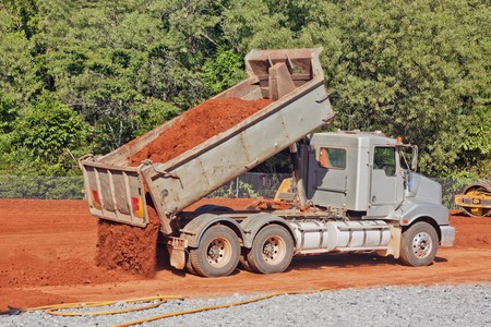 A tip truck is dumping red dirt or soil at a construction site Stock Photo