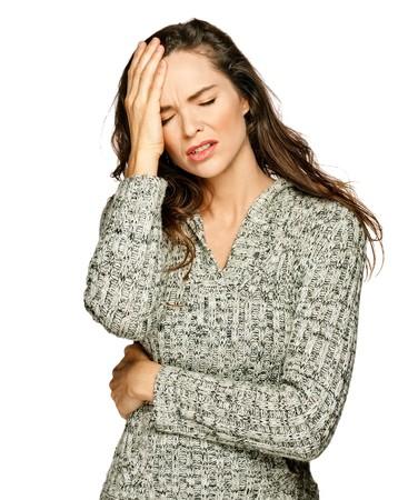 agotado: Una joven mujer atractiva que sufren de enfermedad o dolor de cabeza la celebraci�n de su cabeza. Isolateed en blanco.