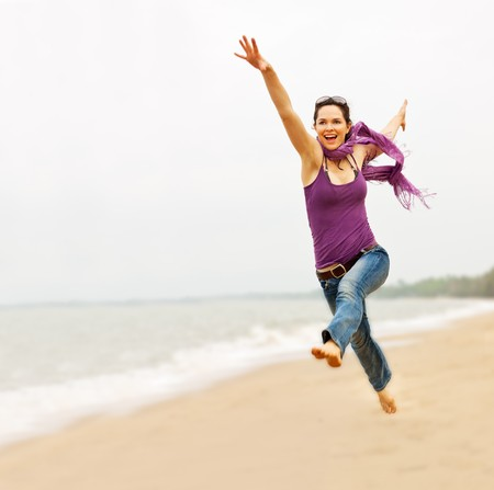 fit on: A beautiful energetic young woman taking a great leap on the beach