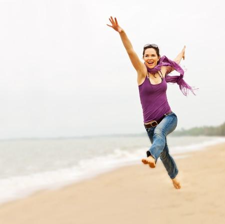 saludable: Una en�rgica joven y bella mujer teniendo un gran salto en la playa