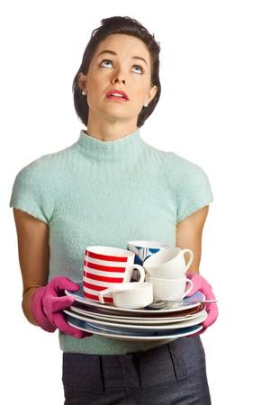 casalinga: Ritratto di una giovane casalinga bella azienda una pila di piatti sporchi e cercando stanchi. Isolato su bianco.  Archivio Fotografico