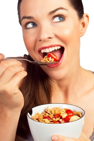 A close-up portrait of a beautiful young woman eating a healthy bowl of cereal with strawberries. Isolated over white. Stock Photo - 7966305