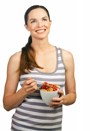 Portrait of a beautiful young woman smiling and holding a healthy bowl of cereal with strawberries. Isolated over white. Stock Photo - 7966306