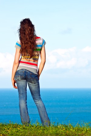 The back of an attractive young woman relaxing and looking at the ocean view photo