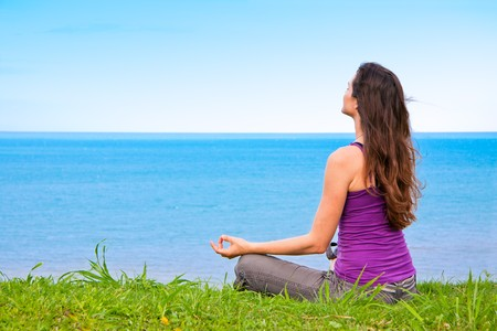 A beautiful young woman sitting meditating with a view of the ocean Stockfoto