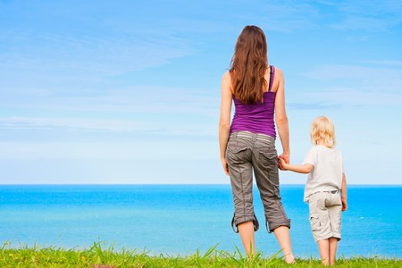 A young mother and child holding hands and looking at beautiful ocean view