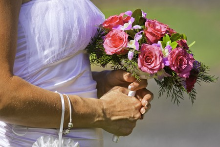 A closeup shot of a bride holding a beautiful bouquet of red and pink flowers on her wedding day Stock Photo - 8276237