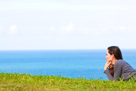 A sad and depressed young woman lying in the green grass looking sadly at  the ocean Stock Photo - 8276225