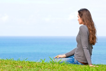 A beautiful sad and unhappy young woman sitting in the green grass looking at the ocean Stock Photo - 8276227
