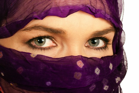 A closeup of a very beautiful Indian or asian woman wearing a purple veil photo