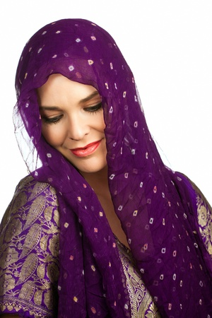A beautiful young Indian or asian woman wearing a head scarf looking down smiling. Isolated over white Stock Photo - 8592893