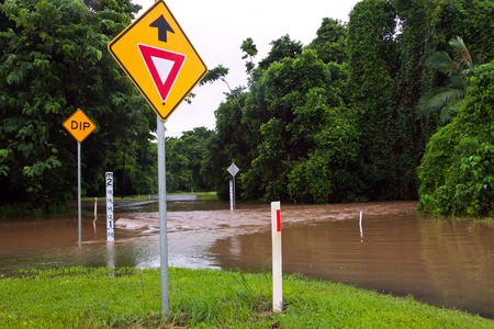 Flooded road with depth indicators and give way and dip road signs  after heavy rain and flooding in Queensland, Australia Stock Photo - 8697777