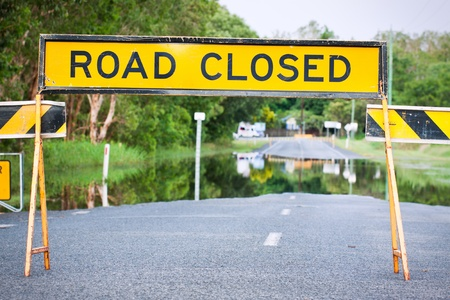 A road closed sign on a flooded road in Queensland, Australia