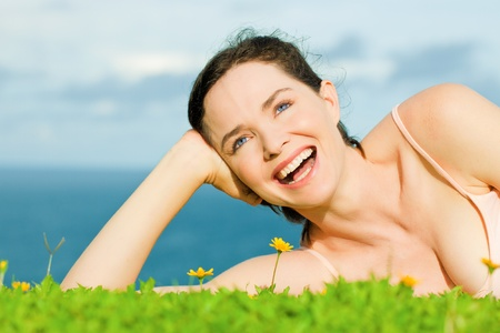 Beautiful young happy woman laying in green grass with yellow flowers photo