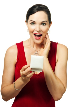 Surprised beautiful young woman holding an open jewellery gift box and looking at camera. photo