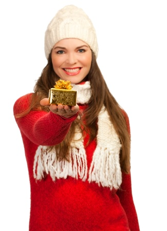 An isolated portrait of a beautiful young woman holding out a small Christmas present. Focus on the present. photo