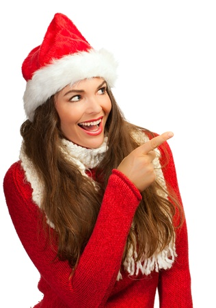 A beautiful young smiling woman wearing a Santa hat and pointing to copyspace photo