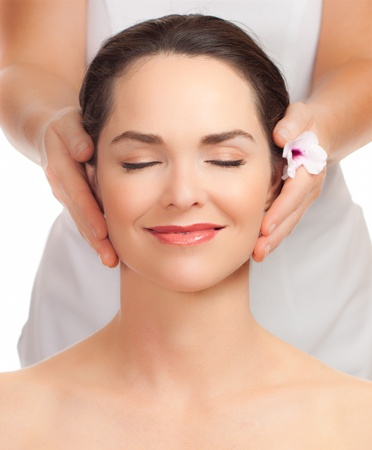 head massage: A portrait of a beautiful young woman getting a face massage Stock Photo