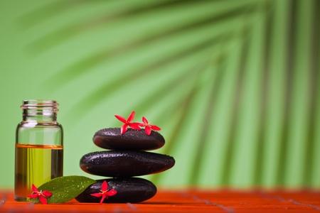 Health spa & massage still life of massage oil and balancing rocks. photo