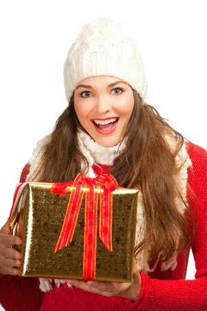 A beautiful young woman smiling and holding a golden christmas present photo