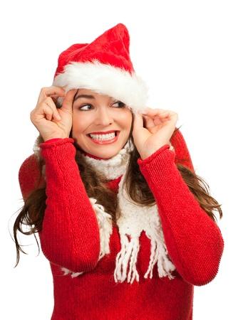 dona: Una atractiva mujer joven sonriente y mirando hacia fuera de un sombrero de Papá Noel. Aislado en blanco.
