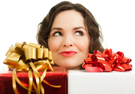 beautifully wrapped: Beautiful young woman peeking over beautifully wrapped Christmas gifts and looking at copyspace Stock Photo